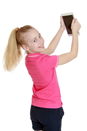blond girl sees the tablet holding it at arms length - isolated on white. photo