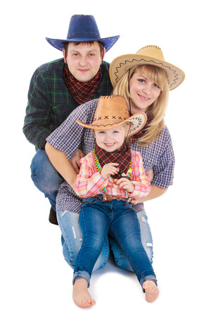 three persons: Young family of three persons in the stylish American cowboy costumes - isolated on white.