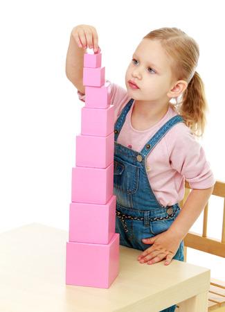 Klein meisje verzamelt de roze ontwikkeling pyramid.Childhood onderwijs in de Montessori school-concept. Geïsoleerd op een witte achtergrond.