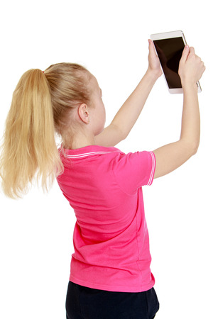 sees: blond girl sees the tablet holding it at arms length, turning away from the camera - isolated on white.