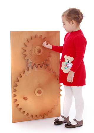 montessori: smart little girl turns the gears in the Montessori classroom - isolated on white. Stock Photo