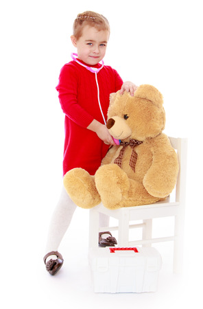 cute little girl playing in the hospital with a teddy bear - isolated on white. photo