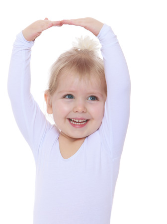 arms above head: cheerful little ballerina raised her arms above her head, the photo on the belt - isolated on white. Stock Photo