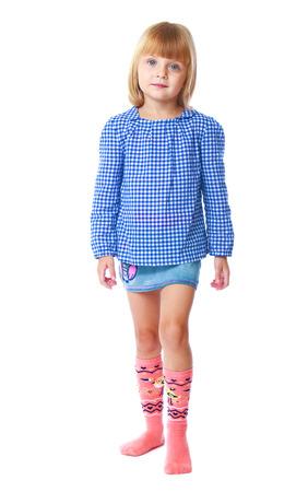 niña encantadora en una blusa y una falda de mezclilla de color azul sobre fondo blanco Foto de archivo