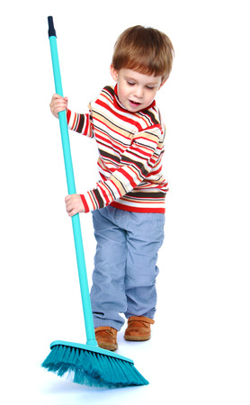 vrolijke jongen vegen de vloer met een borstel - geïsoleerd op wit. Stockfoto
