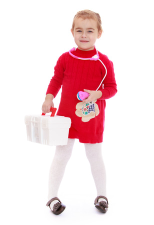Positive little girl with a first aid kit in the hands of - isolated on white. photo