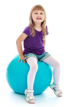petite fille avec robe: Tr�s mignonne petite fille assise sur un gros sports de balle. Enfance heureuse, de la mode, le concept de l'humeur automnale. Isol� sur fond blanc