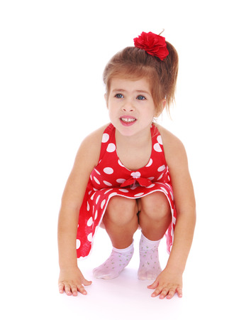 Caucasian little girl squatted down and looking at the camera - isolated on white.