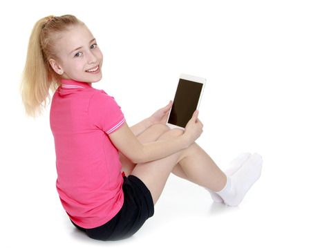 Positive little girl sitting on the floor considering tablet computer - isolated on white. photo