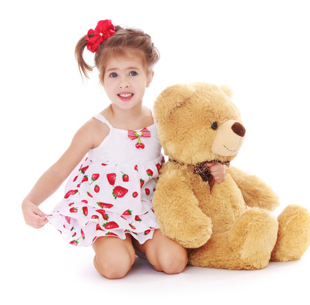 Glimlachend meisje in een de zomerkleding met Teddybeer - op witte achtergrond wordt geïsoleerd die Stockfoto