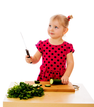 The little girl is preparing salad - isolated on white background