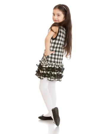 dark haired: Dark haired girl posing in a plaid dress and white stockings - isolated on white background Stock Photo