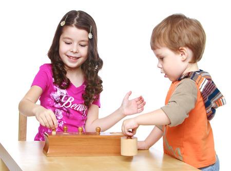 Broer en zus spelen aan de tafel .- Geïsoleerd op een witte achtergrond