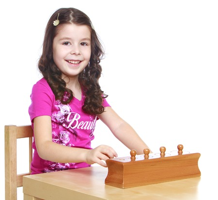 montessori: Smart girl  sitting at the table  learning Montessori material- isolated on white background