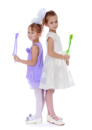 girl magic wand: two well-dressed girl holding a magic wand- isolated on white background Stock Photo