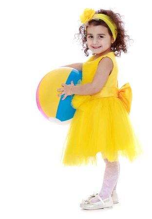 white trim: A trim little dark-haired girl in a yellow dress with striped inflatable ball in his hands- isolated on white background