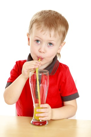 drank: Beautiful blond boy drank through a straw big glass of juice, sitting at the table- isolated on white background
