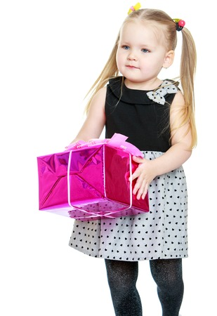 ponytails: Adorable little girl with long ponytails on her head holding a beautifully wrapped gift-Isolated on white background