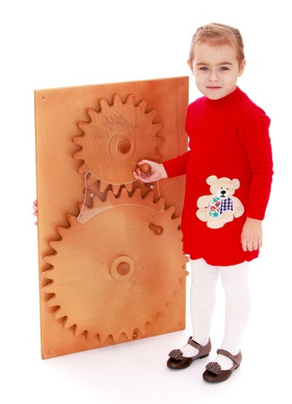 montessori: Little girl turns by hand gear wheels in Montessori kindergarten-Isolated on white background Stock Photo