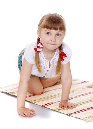 montessori: Adorable little girl with long braids on his head plays on the rug . Montessori kindergarten-Isolated on white background Stock Photo