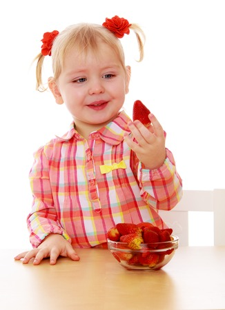 bacon portrait: Adorable little girl holding a strawberry sitting at the table-Isolated on white background
