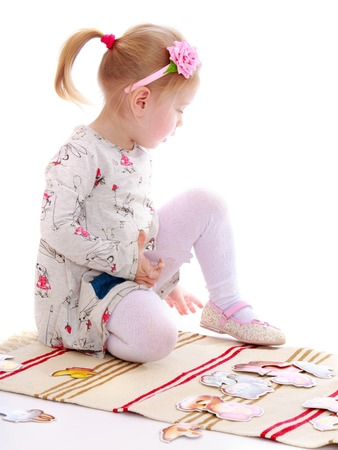 montessori: Little girl in a Montessori kindergarten playing sitting on the Mat-Isolated on white background Stock Photo