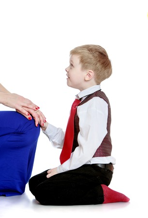 admires: Stylish little boy on his knees admires her mother-Isolated on white background