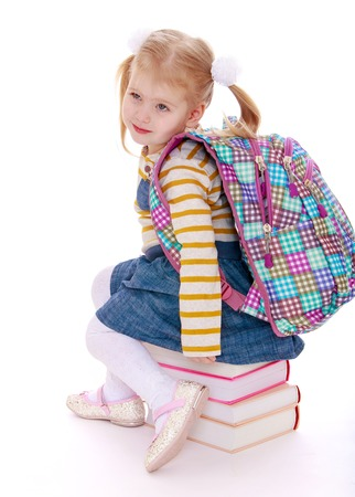 knapsack: little girl  blonde  with a school knapsack on his back  sitting on a stack of books-isolated on white background Stock Photo