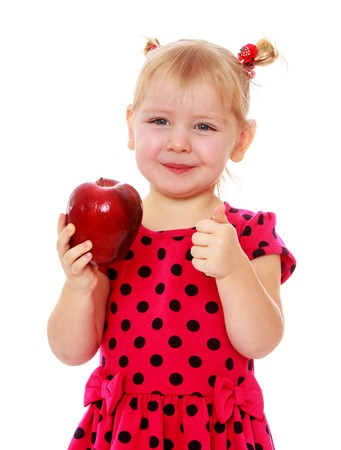 Adorable little blonde with a red Apple in his hand , close-up-isolated on white background photo