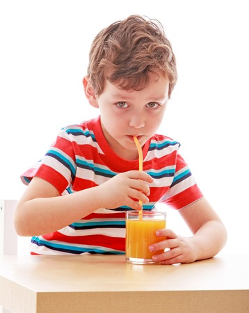 a straw: boy drinks from a glass of orange juice through a straw while sitting at table , close-up-isolated on white background Stock Photo