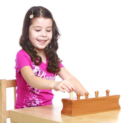 De donkerharige meisje in een Montessori kleuterschool werkt met een puzzel geïsoleerd op een witte achtergrond