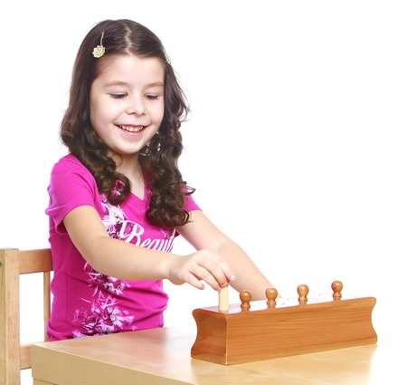 The dark-haired little girl in a Montessori kindergarten works with a puzzle-isolated on white background