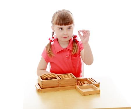 Het meisje in de Montessori-omgeving, studeert het materiaal, ze houdt in haar hand een kraal die wordt gebruikt voor het leren van wiskunde-geïsoleerde op witte achtergrond Stockfoto
