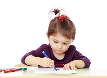 keen: Keen little girl draw with felt-tip pen sitting at the table-isolated on white background Stock Photo