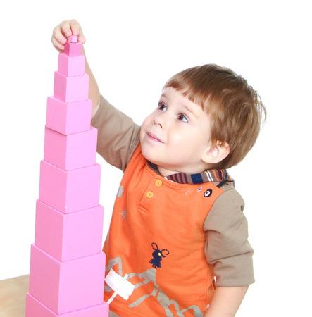 De kleine jongen in Montessori kleuterschool verzamelt roze piramide-Geïsoleerd op witte achtergrond Stockfoto