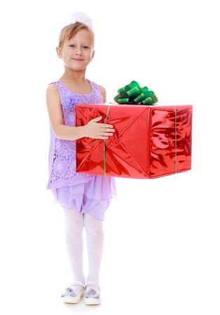 giftwrapped: Festively dressed girl holding a large gift-wrapped box-Isolated on white background