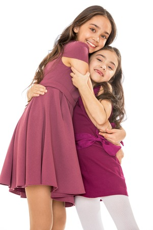 dark haired woman: Dark-haired girl sisters in fashionable dresses hugging, close-up-Isolated on white background Stock Photo