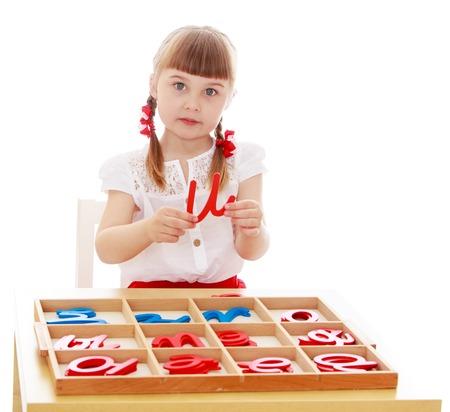 Klein meisje lopen met de letters in Montessori kleuterschool-Geïsoleerd op witte achtergrond