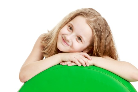 one little girl: Adorable teen girl laid her hands on a big ball-Isolated on white background Stock Photo