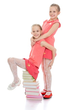 frolic: Charming sisters frolic sitting on a stack of books-Isolated on white background