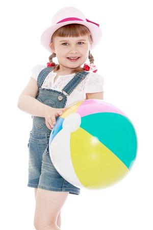 jolie petite fille: fille dans un court salopettes en denim et un chapeau tenant un ballon-Isolé sur fond blanc