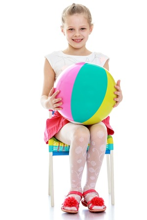 keep your hands: The girl sits on the chair to keep the ball in your hands - isolated on white background