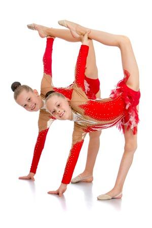 simultaneously: Two girls athletes simultaneously doing sports item - isolated on white background