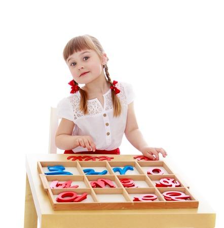 Klein meisje in een Montessori kleuterschool is het bestuderen van de letters - op een witte achtergrond
