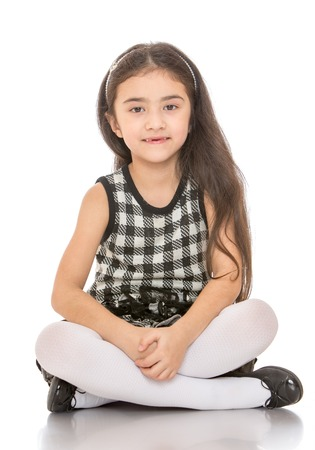 floors: Charming dark-haired little girl sitting on the floor folded in Turkish feet - isolated on white background Stock Photo