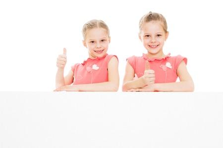niñas gemelas: Muchachas gemelas miran desde detrás de obstáculos - aislado en fondo blanco