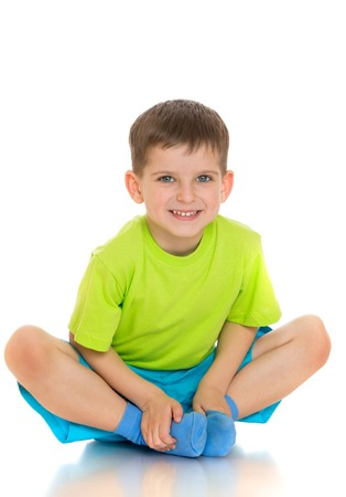 legs folded: The child sits on the floor with folded legs under him - isolated on white background
