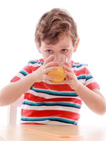 eagerly: The little boy eagerly drinking juice from a glass , close-up - isolated on white background