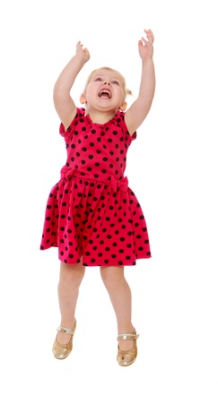 Blonde little girl in a red polka dot dress jumps his arms raised high - isolated on white background