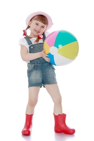 petite fille mignone: Petite fille blonde avec une courte queue de cochon avec un chapeau rose, des combinaisons et des bottes a rassembl� un grand seau de pommes m�res - isol� sur fond blanc